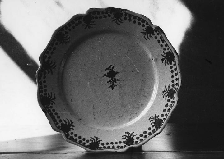 Assiette en faïence au marli chantourné, peint d'une frise de baies et de fleurs, et d'un petit bouquet de fleurs central