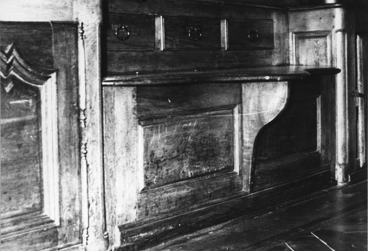 Meuble de pharmacie : détail de la partie inférieure, comprenant un banc-coffre surmonté de 3 tiroirs, bois taillé (détail)