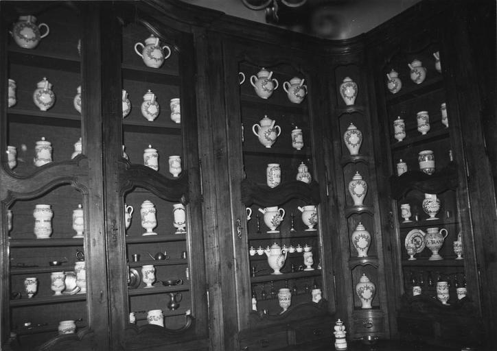 Meuble de pharmacie à plusieurs vantaux vitrés et étagères, décor de moulures chantournées, bois taillé, verre