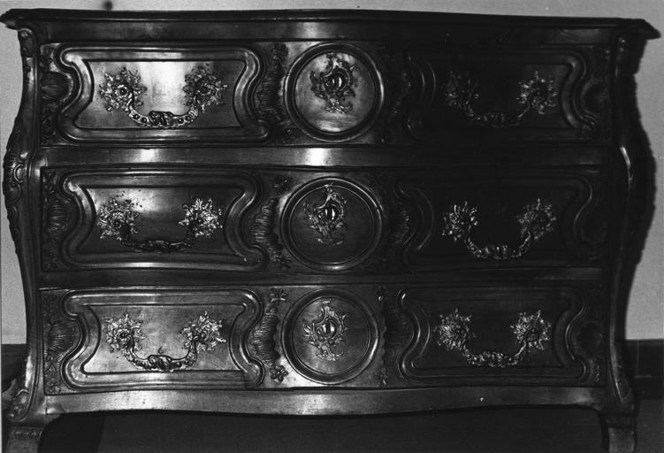 Commode galbée à trois tiroirs en ceinture ornés de coquilles, rocailles et médaillons, noyer taillé, sculpté, poignées et serrures en bronze doré (?)