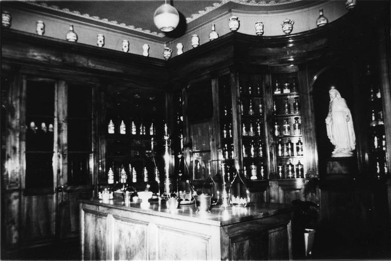 Meuble de pharmacie composé de vitrines, étagères et tiroirs dans la partie supérieure, vantaux dans partie inférieure, bois taillé, cuivre, fer forgé