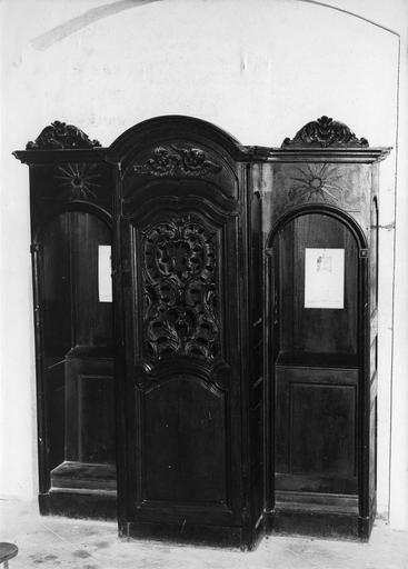 Confessionnal à vantail central cintré, orné d'un motif rocaille sculpté et ajouré, surmonté de deux chérubins, tandis que les loges des pénitents présentent un fronton sculpté d'une coquille, bois taillé
