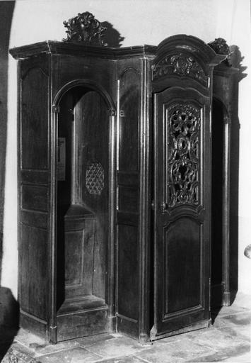 Confessionnal à vantail central cintré orné de motifs rocailles sculptés et ajourés, et d'un cartouche représentant un chien et un arbre, bois taillé, sculpté