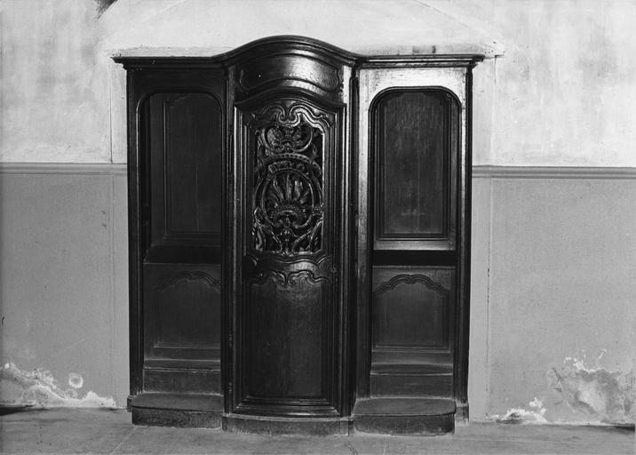 Confessionnal à porte centrale cintrée et galbée, sculptée et ajourée de motifs de rocailles, bois taillé, sculpté