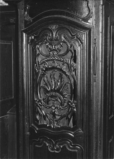 Confessionnal : détail du décor sculpté et ajouré de motifs rocaille du vantail central, bois sculpté
