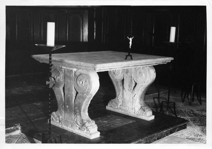 Table de chasse en pierre, aux deux pieds sculptés de deux volutes terminées par des pattes griffues encadrant un pilastre, actuellement utilisée comme autel