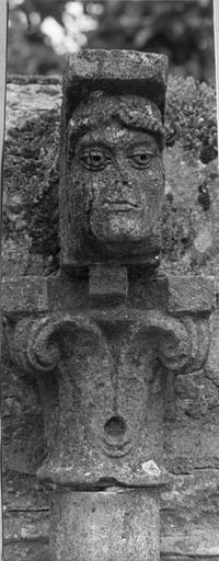 Colonnette : détail d'un chapiteau composite surmonté d'un modillon orné d'un visage de personnage aux cheveux tressés, pierre sculptée (détail)