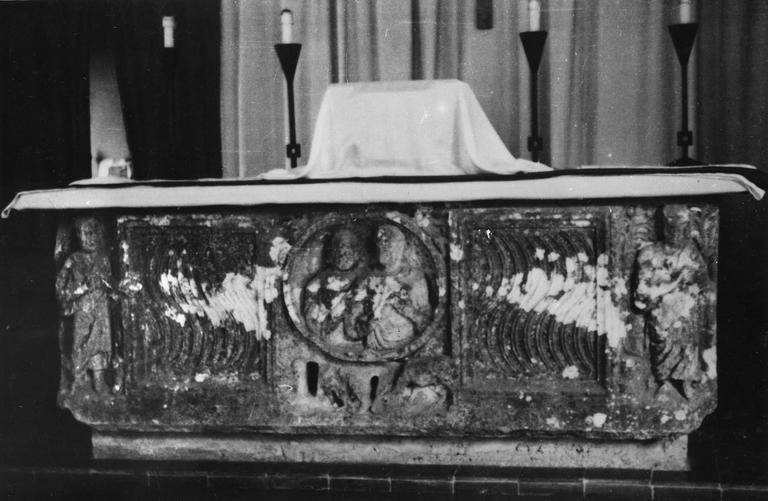 Sarcophage sculpté de deux personnages aux angles, d'un médaillon central abritant 2 autres personnages et de deux panneaux à décor de cannelures ondulées, utilisé comme autel, pierre sculptée