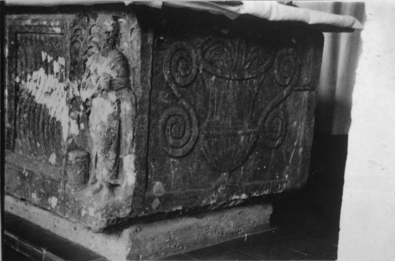 Sarcophage : détail du décor de vase  à anses d'un des petits côtés, ainsi que d'un des personnages des angles, sculpté en demi-relief, pierre sculptée (détail)