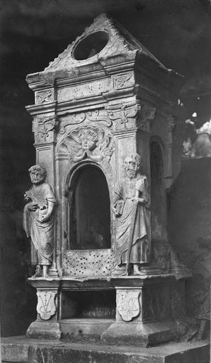Tabernacle architecturé, orné d'une niche au fronton en coquille, de chapiteaux à motifs végétaux et de saint Pierre et saint Jean en très haut relief.