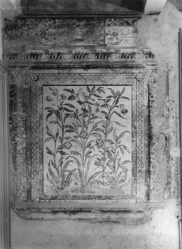 Peinture monumentale : salle des Commissions, détail d'un panneau feint orné de fleurs et d'un oiseau, dans un encadrement d'architecture feinte, surmonté d'une frise au décor de rinceaux et de putti