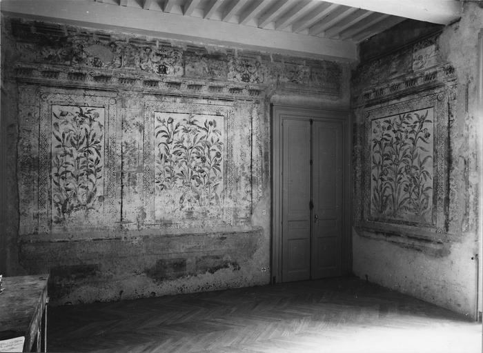 Peinture monumentale : vue de l'angle sud-est de la Salle des Commissions au décor représentant une architecture feinte aux trumeaux peints de panneaux fleuris