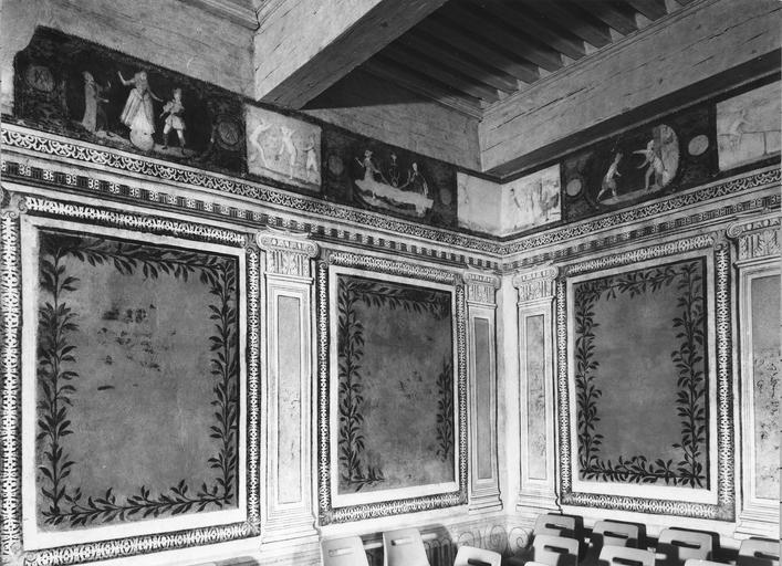 Peinture monumentale : salle du Conseil, détail du décor en trompe l'oeil représentant des éléments d'architecture, des panneaux aux cadres feints, une frise ornée de plusieurs scènes animées de personnages