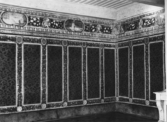 Peinture monumentale : salle des brocarts, décor en trompe l'oeil imitant des panneaux de brocart encadrés par des guirlandes de fleurs, surmontés d'une corniche feinte dont la frise présente plusieurs scènes animées de personnages