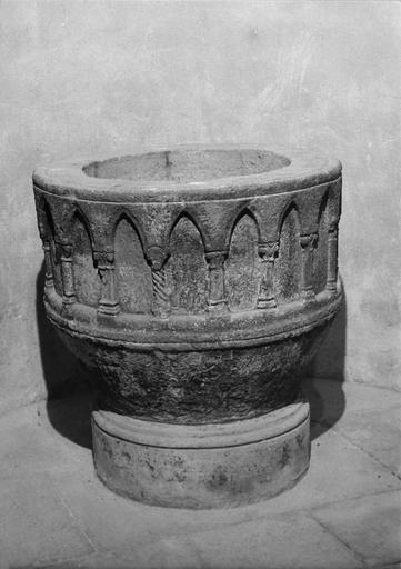 Fonts baptismaux : cuve circulaire sculptée d'une série d'arcs brisés, supportés par des colonnettes ou des pilastres aux fûts et aux chapiteaux différents, granit taillé, sculpté