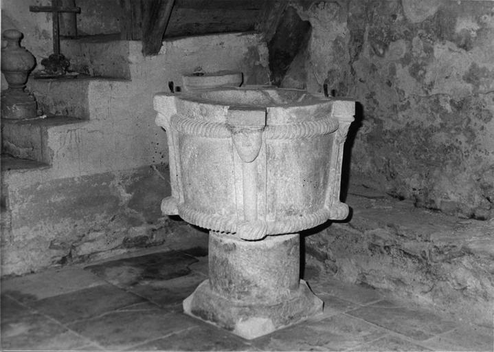 Fonts baptismaux : cuve circulaire sculptée de colonnettes aux chapiteaux feuillagés ou figurés, reliées par une corde sculptée, pierre taillée
