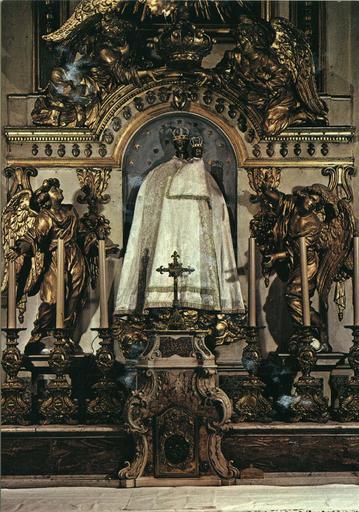 Retable, tabernacle, gradin d'autel : retable à simple corniche cintrée surmonté d'anges qui soutiennent une couronne, niche abritant une statue de la Vierge à l'Enfant encadrée par deux statues d'anges, tabernacle orné de volutes de style rocaille, bois sculpté, peint, doré (détail)