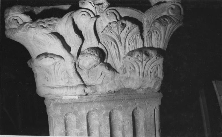 Chapiteau : décor sculpté de volutes, de rangées de feuilles d'acanthe et d'un ange, actuellement utilisé comme bénitier, pierre sculptée (détail)