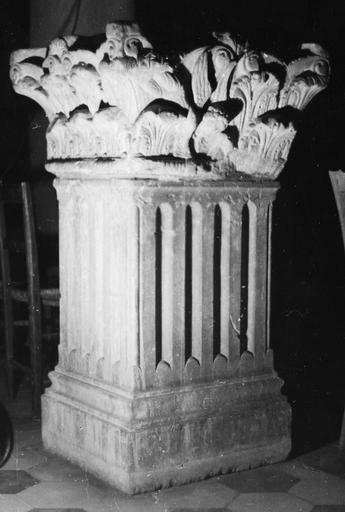 Chapiteau : décor sculpté de volutes, de rangées de feuilles d'acanthe et d'un ange, monté sur un pilier de section carrée à fût cannelé, actuellement utilisé comme bénitier, pierre sculptée