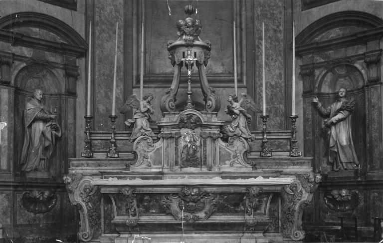 Autel sculpté d'un cartouche central à l'Agneau et aux chérubins, gradin d'autel, tabernacle architecturé surmonté d'une exposition en forme de dais cantonnés d'anges adorateurs, marbre sculpté