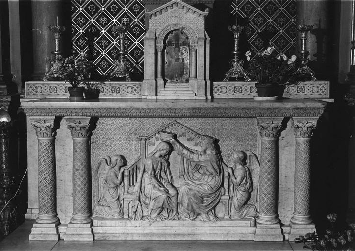 Autel : bas-relief central représentant le couronnement de la Vierge, sur fond de rinceaux stylisés, encadré par des colonnes à chapiteaux composites, marbre