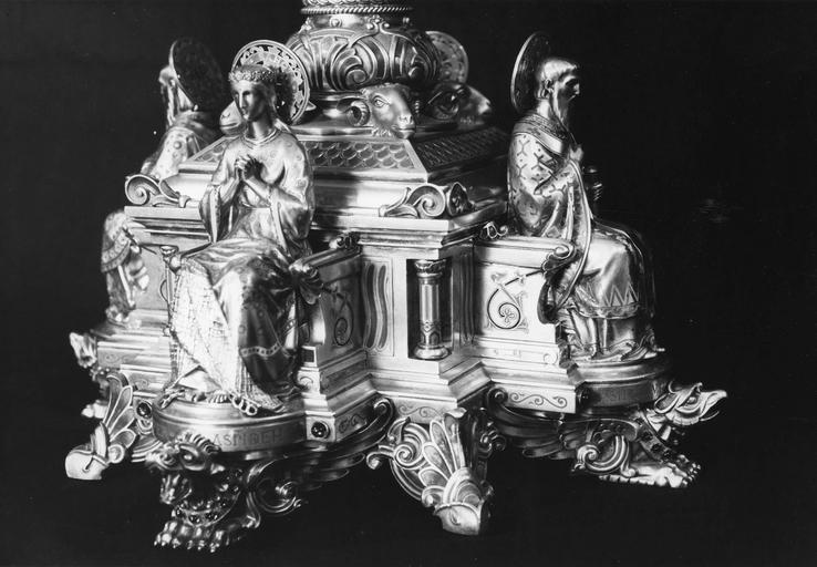 Ostensoir : détail d'une sainte et d'un saint personnage assis sur des trônes, sur le socle de l'ostensoir, bronze doré, émail, pierres (détail)
