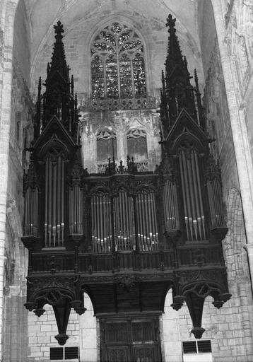 Partie instrumentale de l'orgue au décor sculpté  reprenant l'architecture d'une église gothique, avec pignons et pinacles, bois sculpté