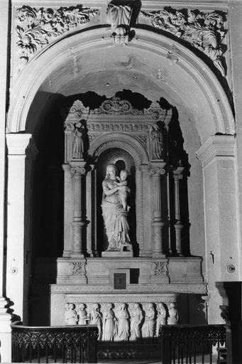 Autel, tabernacle, retable, groupe sculpté : Vierge à l'Enfant, retable architecturé creusé d'une niche encadrée par des colonnettes surmontées d'anges, marbre et pierre sculptés