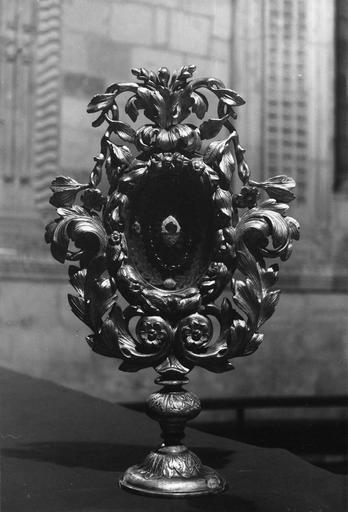 Reliquaire : lunule entourée de rinceaux végétaux et de frises de fleurs, bois sculpté, doré