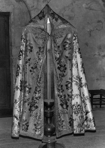 Chape de soie brochée au motif répétitif de branchages fleuris et d'épis de blé, chaperon bordé d'un galon frangé en fils de métal (avers)