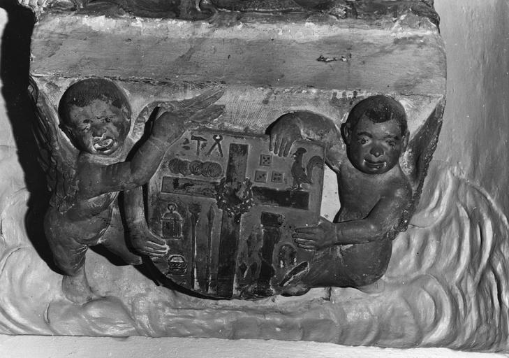 Groupe sculpté : Vierge de pitié, détail des 2 angelots et de l'écu aux instruments de la Passion qu'ils tiennent, pierre sculptée, peinte