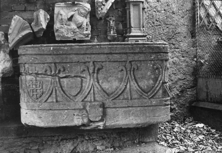 Cuve baptismale sculptée d'une frise de fers de lances et de raies de coeur, ainsi que d'un animal sur le dos duquel repose un écu, pierre sculptée