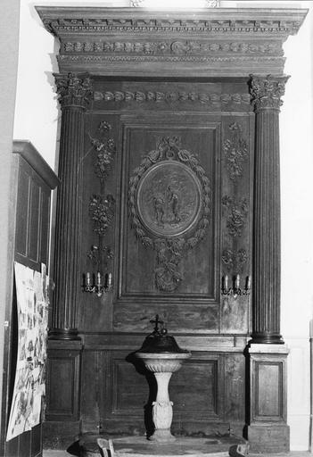 Lambris architecturé au panneau central sculpté d'un médaillon représentant le Baptême du Christ, de guirlandes de feuillages et de chutes de fruits, bois sculpte