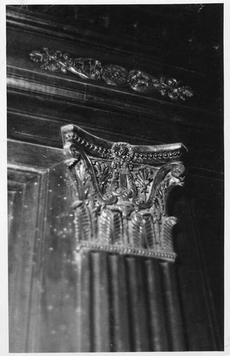 Lambris de revêtement : détail d'un chapiteau composite au feuilles d'acanthe remplacées par des palmettes, lyre sculptée au centre, frise de perles, bois sculpté