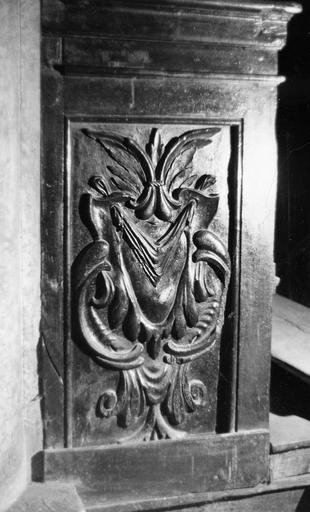 Stalles : détail de la partie inférieure d'une jouée, ornée d'un motif de cartouche, bois sculpté