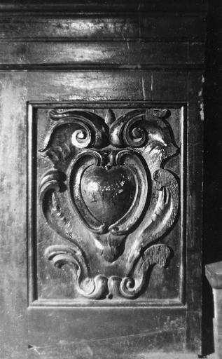 Stalles : détail de la partie inférieure d'une jouée, ornée d'un motif de cartouche aux cuirs, bois sculpté