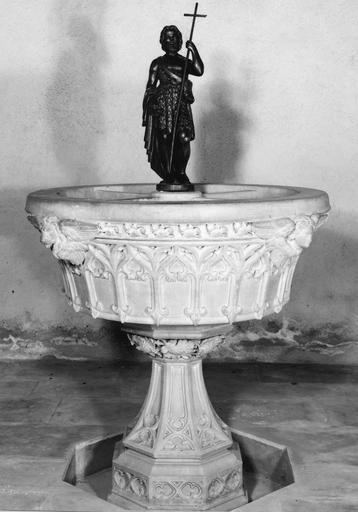 Fonts baptismaux au décor sculpté d'éléments architecturés néo-gothiques, de mascarons aux symboles des évangélistes, et surmonté d'une statue de saint Jean-Baptiste, pierre sculptée, bronze