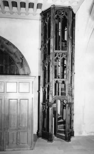 Tribune des Pénitents : détail d'un des escaliers en forme de tour au décor architecturé néo-gothique, bois sculpté, ajouré