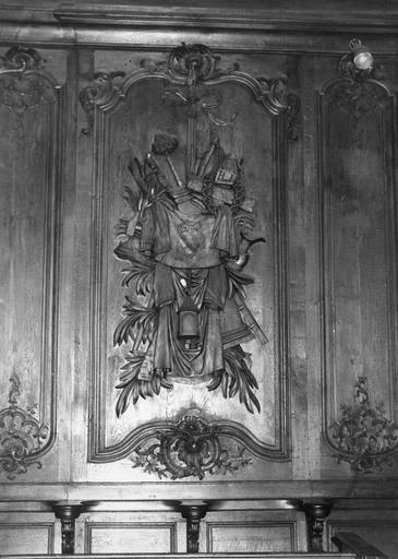 Lambris de revêtement : détail d'un panneau sculpté en bas-relief d'un trophée aux attributs de la Passion