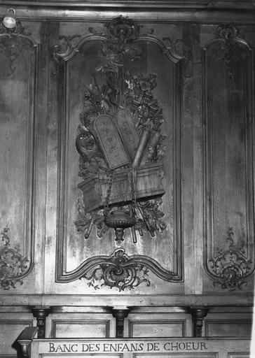 Lambris de revêtement : détail d'un panneau sculpté en bas-relief d'un trophée comprenant entre autres, l'Arche d'alliance, les tables de la Loi, bois sculpté