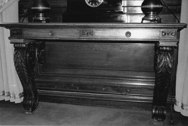 Console à deux pieds en forme de volutes sculptées de motifs végétaux, deux tiroirs en ceinture, bois taillé, sculpté