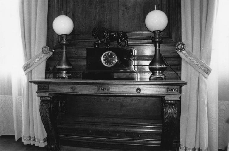 Console à deux pieds sur laquelle sont posées une pendule au lion et deux lampes