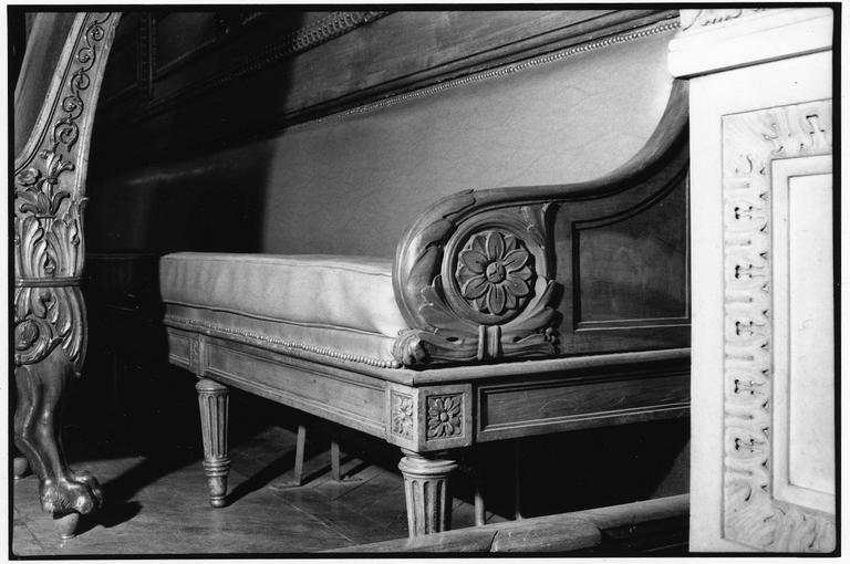 Banc à pieds fuselés et cannelés, ceinture droite moulurée et sculptée de rosaces, deux accotoirs à enroulement sculpté d'une volute et d'une fleur, garniture à carreau, dit de type 2, bois taillé, sculpté, skaï