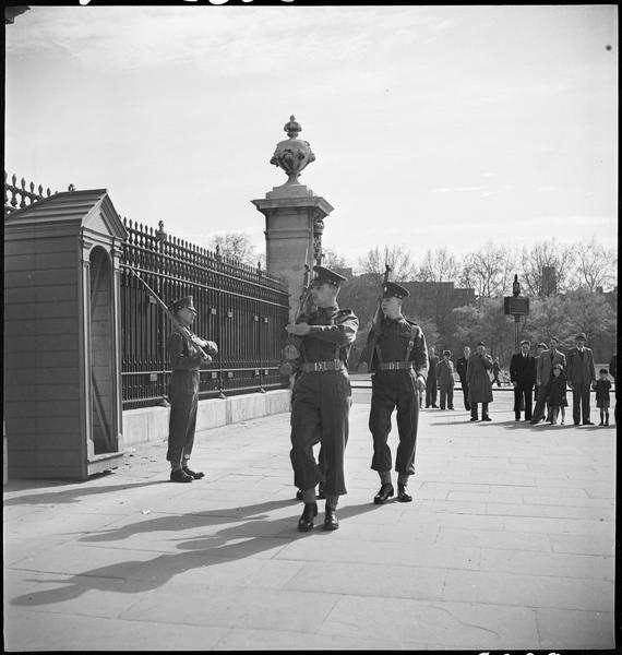 La relève de la garde devant les grilles du palais : les touristes s'arrêtent pour regarder