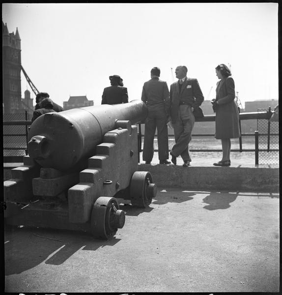 Touristes et affût de canon disposé le long du fleuve avec le pont en fond