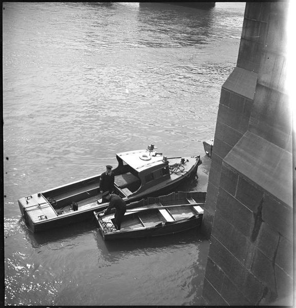 Deux embarcations de la police fluviale près de la pile d'un pont