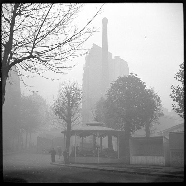 Manège et cheminée d'usine dans le brouillard