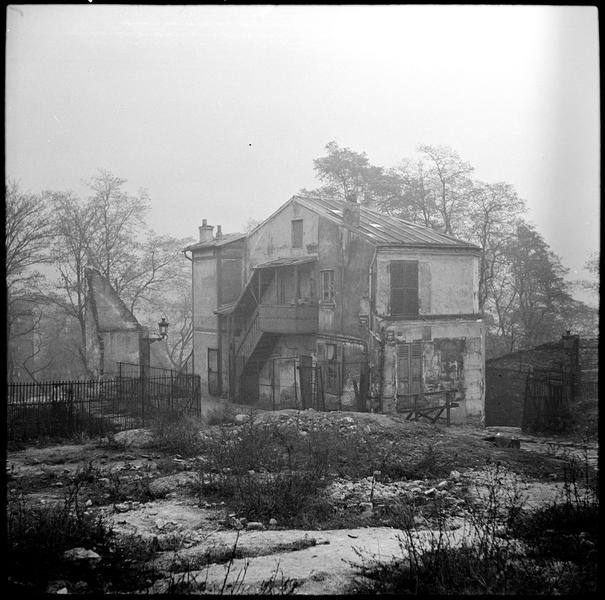 Terrain vague et maison semblant abandonnée saisis dans le brouillard