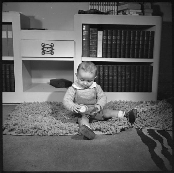 Garçonnet - enfant Baudet - assis sur un tapis devant un meuble bibliothèque