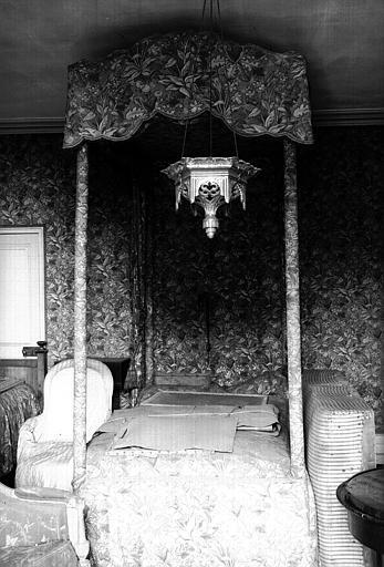 Un lit Louis XVI à quatre colonnes garni, comme les murs de la pièce de cretonne du XIXème, avec son baldaquin (chambre du midi du premier étage, côté cour)